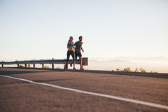 Couple on morning run. Outdoor shot of young couple on morning run. Young men and women jogging on country road Royalty Free Stock Image
