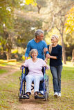 Couple mother walk. Loving middle aged couple taking disabled mother for a walk outdoors Stock Photography