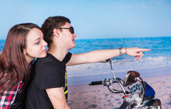 Couple on Motorbike at the Beach Looking to Right. Close up Young Couple Riding a Motorbike at the Beach While Looking and Pointing to the Right of the Frame Stock Photography