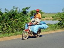 Couple on a motorbike. Man and woman with belongings riding on a motorbike in the countryside, Cambodia Stock Images