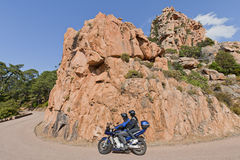 Couple on motorcycle driving in Corsica, France. Bikers in Corsica, France driving on bending road going downhill. Focus was on the rocks Royalty Free Stock Images
