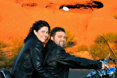 Couple on Motorcycle in Front of Red Rock. A couple in leather jackets sit on a motorcycle in front of red rocks in the Arizona desert Stock Images