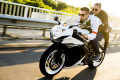 Couple on motorcycle. Man and women wearing  leather jackets and stylish sunglasses riding on motorcycle Royalty Free Stock Photos