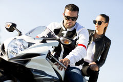Couple on motorcycle. Man and women wearing leather jackets and stylish sunglasses riding on motorcycle Stock Photo