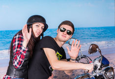 Couple on Motorcycle Waving to Camera at Beach Royalty Free Stock Image