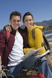 Couple With Mountain Bike And Roadmap. Portrait of happy Caucasian couple with mountain bike and roadmap Stock Photos