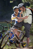 Couple on mountain bikes laughing and looking at map Royalty Free Stock Images