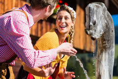 Couple at mountain hut drinking water from source Stock Images