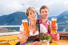 Couple on mountain hut drinking wheat beer Stock Photography