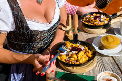 Couple on mountain hut eating Kaiserschmarrn. A traditional Austrian pancake Royalty Free Stock Photography