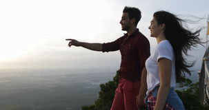 Couple at mountain top holding hands, latin man showing woman morning view point finger. Slow Motion 60 stock footage