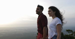 Couple at mountain top holding hands, latin man and woman enjoy morning view