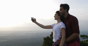 Couple On Mountain Top Taking Selfie Photo On Cell Smart Phone, Man And Woman Embracing At Sunrise Happy Smiling stock video footage