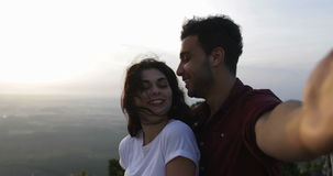 Couple On Mountain Top Taking Selfie Photo At Sunrise, Hispanic Man And Woman Happy Smiling. Slow Motion 60 stock video