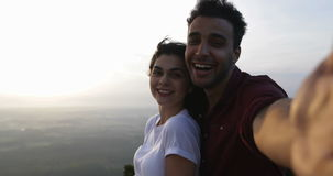 Couple on mountain top taking selfie photo at sunrise, latin man and woman happy smiling. Slow Motion 60 stock video