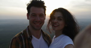 Couple on mountain top taking selfie photo at sunrise, tourists man and woman happy smiling. Slow Motion 60 stock video