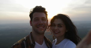 Couple on mountain top taking selfie photo at sunrise, tourists man and woman happy smiling stock footage