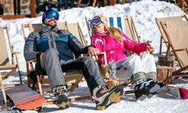 Couple at mountains in winter laughing and relax in sunbed. Happy couple at mountains in winter laughing and relax in sunbed Stock Photography