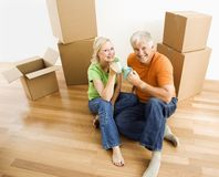 Couple with moving boxes. Middle-aged couple sitting on floor among cardboard moving boxes with coffee