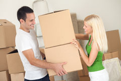 Couple moving boxes. Smiling couple carrying moving boxes Stock Image