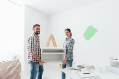 Couple moving furnishings in their new house. Young happy couple renovating their new house and moving furnishings together Stock Photo