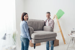 Couple moving furniture in their new house. And doing home renovations, they are carrying an armchair Royalty Free Stock Photo