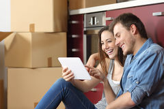 Couple moving home and buying online. With a tablet sitting on the floor in the kitchen Royalty Free Stock Image