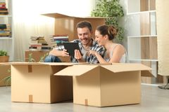 Couple moving home checking tablet content stock images