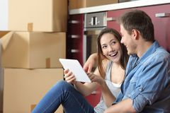 Couple moving home checking tablet online content. Happy couple moving home checking tablet online content sitting on the floor of the kitchen stock photography