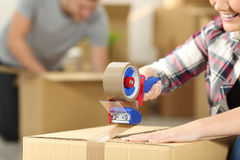 Couple moving home packing boxes. Close up of a happy couple moving home packing boxes and sealing with tape sitting on the floor royalty free stock photos