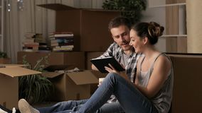 Couple moving home planning reform using a tablet. Happy couple moving home planning reform using a tablet sitting on the floor in the night