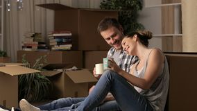 Couple moving home resting drinking coffee stock video footage