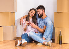 Couple moving home. Young happy couple drinking wine, celebrating moving to new home, moving to a new home Royalty Free Stock Photos