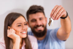Couple moving home. Young happy couple holding keys to new home, moving to a new home Royalty Free Stock Image