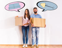Couple moving home. Young happy couple moving to a new home, opening boxes Stock Image