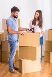 Couple moving home. Young happy couple moving to a new home, opening boxes Royalty Free Stock Images