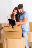 Couple moving home. Young happy couple moving to a new home, opening boxes Stock Photos