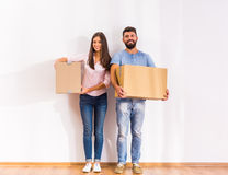 Couple moving home. Young happy couple moving to a new home, opening boxes Royalty Free Stock Image