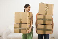 Couple moving house, carrying stack of cardboard boxes, man's face obscured, woman smiling. Couple moving house, carrying stack of cardboard boxes, man's face Royalty Free Stock Photos