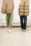 Couple moving house, carrying stack of cardboard boxes, side by side, low section, front view Royalty Free Stock Photography