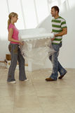 Couple moving house, carrying white chair wrapped in plastic sheet in room, smiling, side view Stock Photo