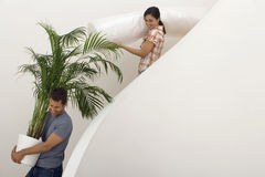 Couple moving house, man carrying large pot plant down staircase, woman carrying dust sheet, smiling. Couple moving house, men carrying large pot plant down Royalty Free Stock Photo