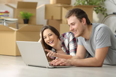 Couple moving house searching on line. Happy casual couple moving house searching information on line in a pc lying on the floor with boxes in the background stock photography