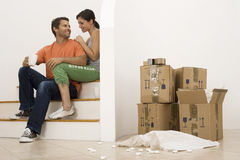 Couple moving house, taking tea break at bottom of staircase near stack of boxes, smiling Stock Photo