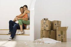 Couple moving house, taking tea break at bottom of staircase near stack of boxes, smiling, portrait Stock Image