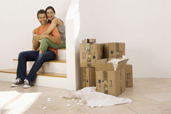 Couple moving house, taking tea break at bottom of staircase near stack of boxes, smiling, portrait Royalty Free Stock Photos