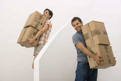 Couple moving house, woman carrying small stack of boxes down staircase, man waiting, smiling Stock Image