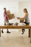 Couple moving house, woman packing crockery in box on dining room table, man carrying sealed boxes Stock Photos