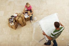 Couple moving house, woman packing crockery in boxes, man carrying table, overhead view Royalty Free Stock Image