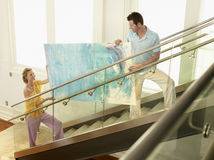 Couple Moving Modern Painting Up Stairs Royalty Free Stock Photo